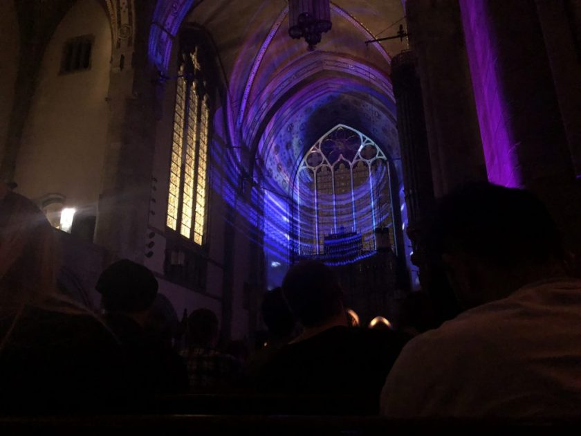 Photo by S. Nicole Lane. Silhouettes of people from the crowd are sitting at the pews. There is a purple circular light shining on the stained glass. To the left, the windows and stained glass have a yellow light. There is a green stream of light on the right side of the image.