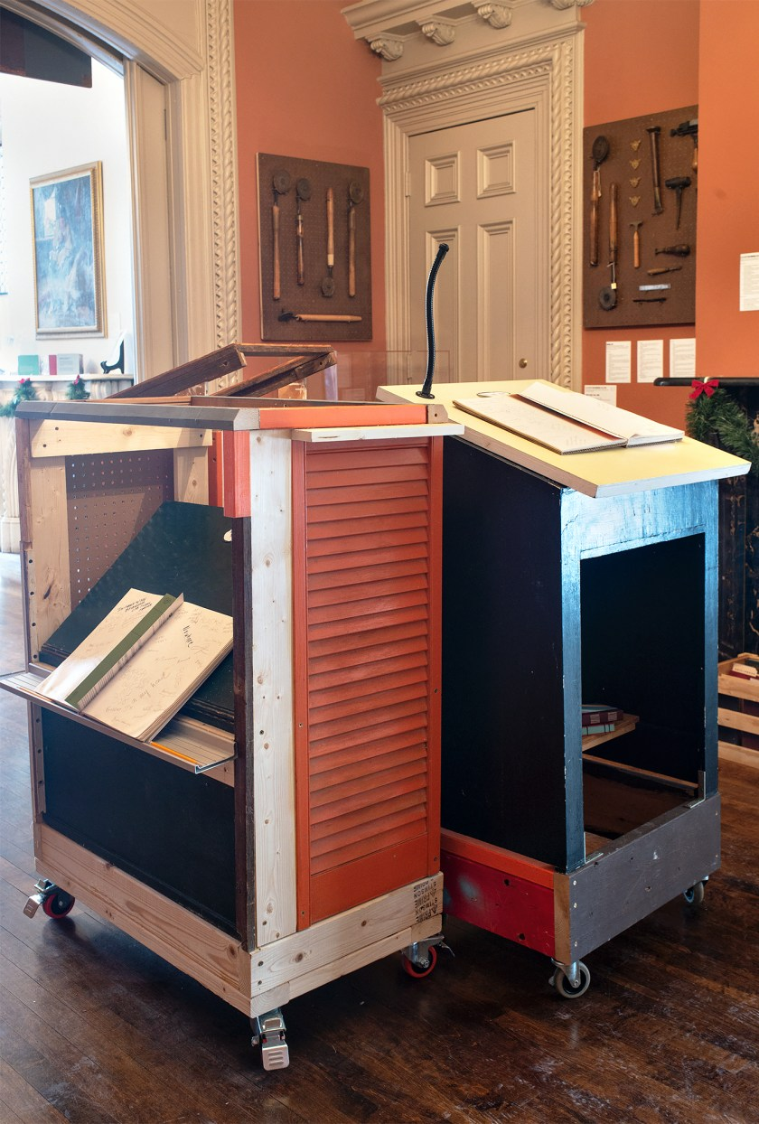 Image: An array of pedestals from the Everything on Wheels project placed in one of the downstairs rooms at Hull-House. The mobile pedestals are made of scrap material (wood, pegboard, milk crates, random fabric, paint, and other reused items) and fitted with wheels on the bottom. Each pedestal contains a book with a different question for people to answer. In the background, various bookbinding tools are displayed on the wall. Photo by Greg Ruffing.