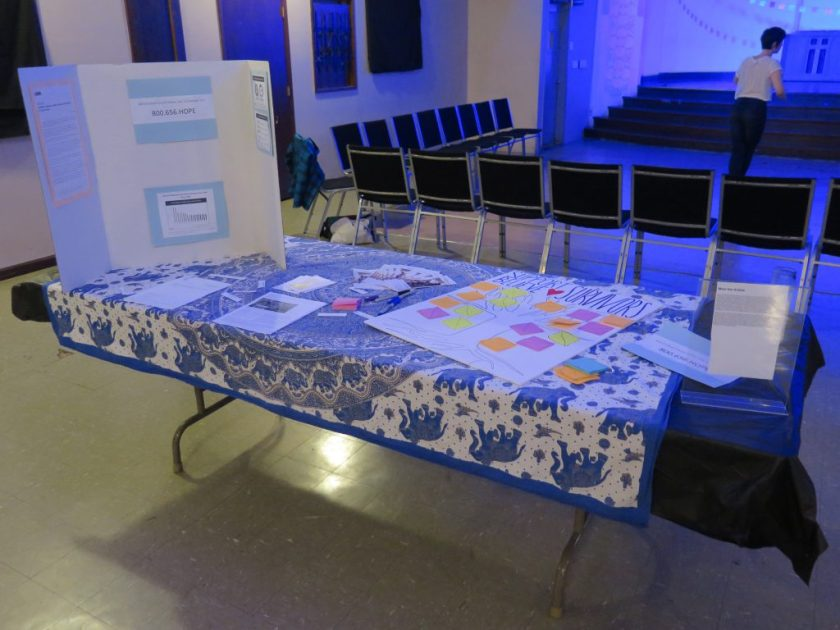 "Image: The interactive display related to Lani T. Montreal and Maxine Patronik's performance ""Blood Memory,"" at the Chicago Danztheatre Auditorium as part of the Body Passages culminating event. In the foreground, a table is covered with blue-and-white elephant-print cloth, a tri-fold posterboard, and various papers, including a large one that reads ""SUPPORT BELIEVE ♡ SURVIVORS"" and shows a drawing of a tree with colorful post-it note leaves. In the background, two rows of chairs and the front of the stage are visible, forming three sides of the square performance area, where one person is standing. Photo by Marya Spont-Lemus."