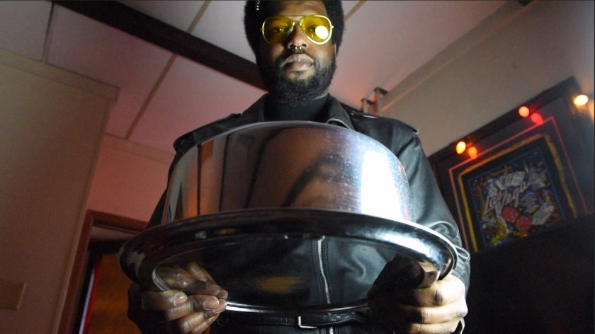 "Image: Film still from ""Thirst Trap"" featuring actor Blackson leaning forward in preparation to serve his queen cake from a stainless steel cake carrier. Photo courtesy of Heather Raquel Phillips."