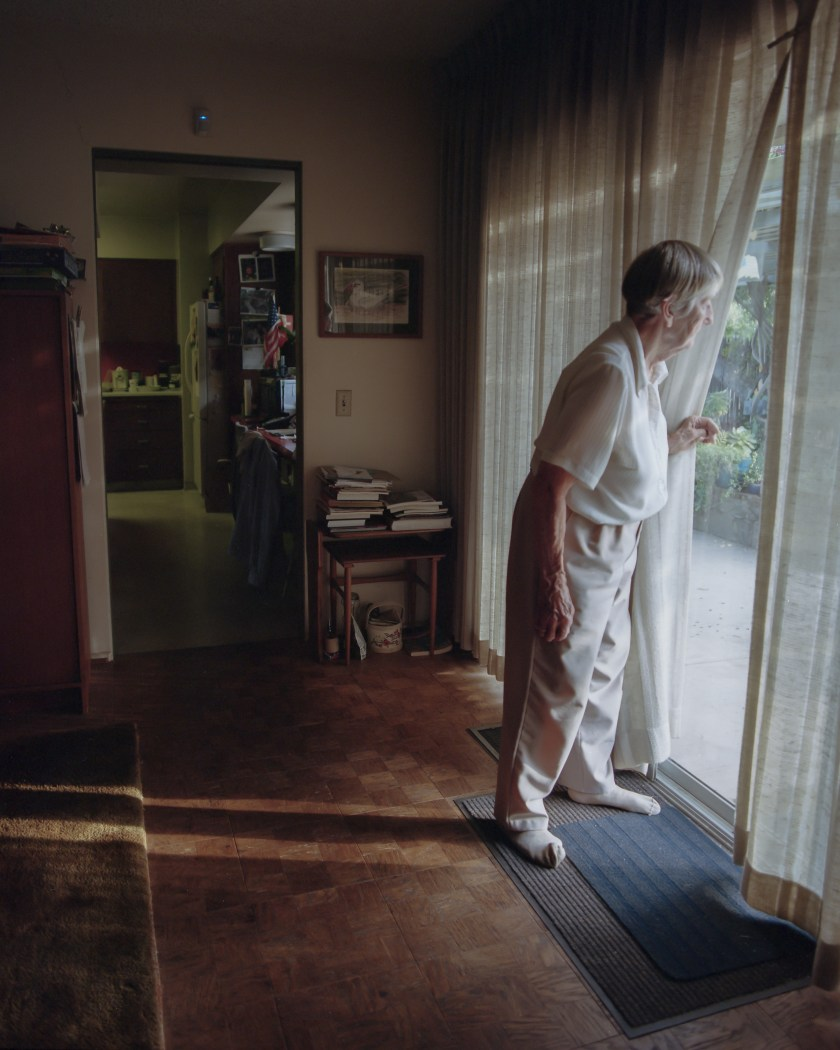 Annamarie Mitchell (Mitch's grandmother) peers through her window that was once shattered during a robbery. She now fears that a similar burglary will happen again and will occasionally check her backyard for trespassers. San Marino, California. Courtesy of Mitch Buangsuwon.