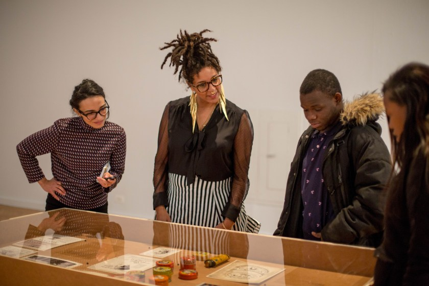 "Image: The author, D. Denenge Duyst-Akpem, and two young visitors look at beauty product containers and printed materials displayed in a vitrine in the ""African American Designers in Chicago"" exhibition at the Chicago Cultural Center. Photo by Ireashia Bennett."