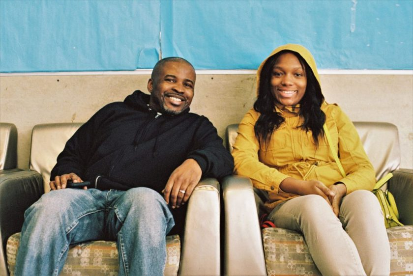 Image: George Wilson and a young woman, a client at BBF Family Services, smiling into camera and sitting on a beige couch at BBF. Photo by Eric K. Roberts.