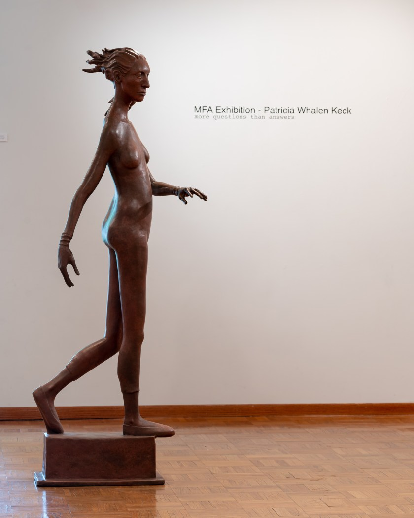 "Image: Patricia Whalen Keck ""The Pedestrian"" Bronze. A large sculpture of a woman in a position that suggest she is walking or crossing across the space. The show title of the exhibition is seen on the wall in the background. Image courtesy of the artist"