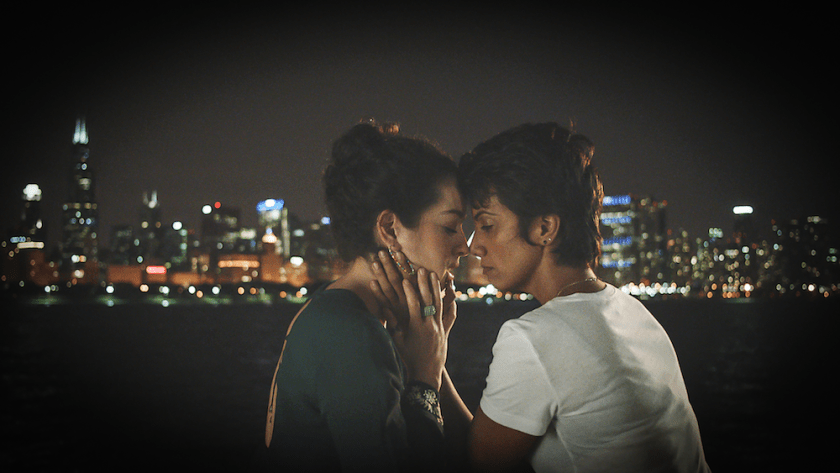 "In the background of this still from the film ""Signature Move,"" the Chicago skyline is lit up and slightly blurred. In the foreground, the characters played by Sari Sanchez (Alma) and Fawzia Mirza (Zaynab) are shown in profile, facing each other with faces touching. Both characters' eyes are closed or almost closed. Alma's hands hold Zaynab's hands, which hold Alma's face. Alma wears a long-sleeved blue-green shirt and Zaynab wears a white t-shirt. The edges of the frame are feathered and dark."