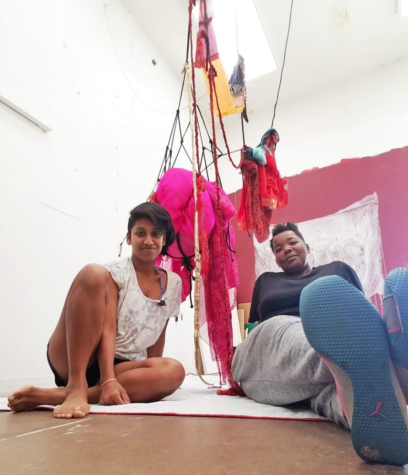 Preetika (left) and Lovie (right) sitting below one of Preetika's installations.