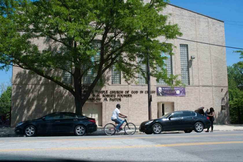 A streetview of Roberts Temple Church of God in Christ on South State Street. It is a sunny day, there is a tree blocking much of the facade. There are two cars parked in front on the street and a person riding a bike. Photo by Tony Smith.