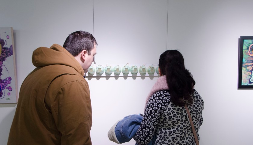 "Two guests closely examine ""Seem"" a piece by EAC member Barbie Perry"