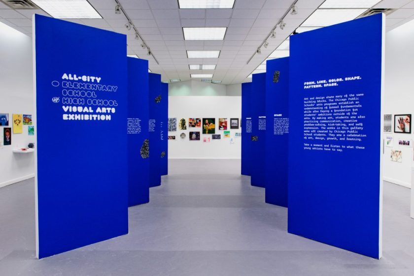 Image: Front view of the All-City High School Visual Arts Exhibition. Blue zigzag walls create a walkway for viewers with art displayed on the surrounding walls. Photo by Ryan Edmund.