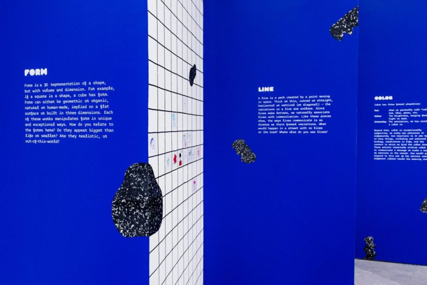 "Image: Detail of the exhibition's constructed blue walls. The wall in the foreground displays the definition of ""Form,"" while the walls in the background display the definitions of ""Line"" and ""Color."" Photo by Ryan Edmund."