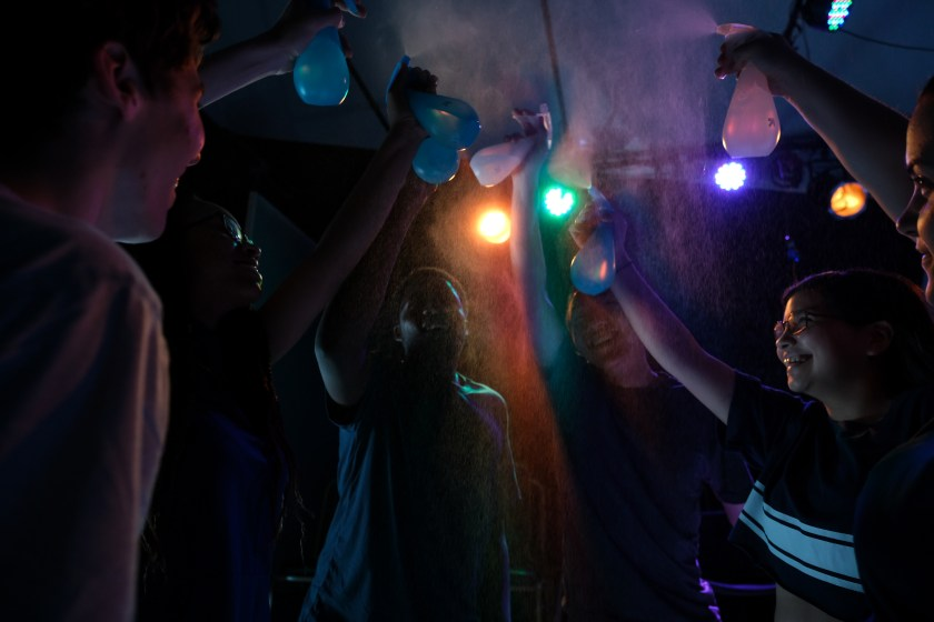 "Image: Six youth performers of ""Parched"" circle and face in towards each other. Their arms extended and holding water bottles, they spritz the air. An orange, green, purple, and yellow lightbulb strung in the air behind them. Image courtesy of Joel Maisonet"