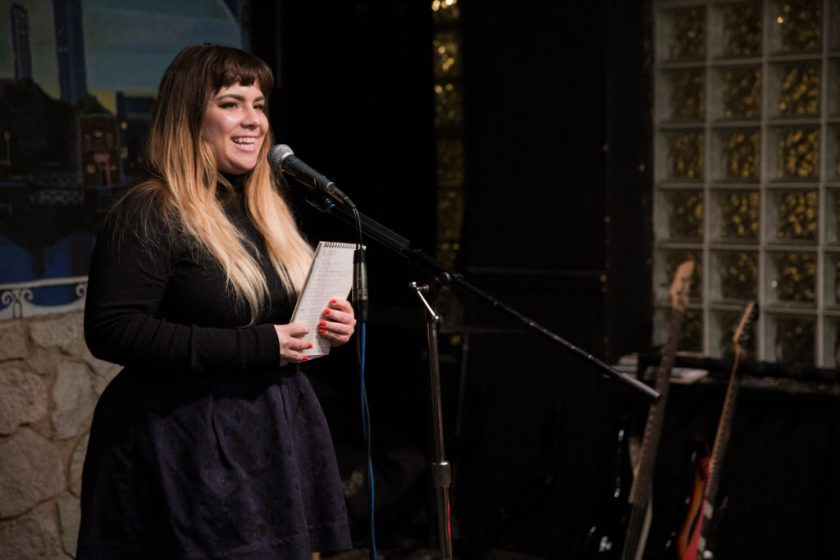 Image: Photo of Gina Wynbrandt performing on-stage at Miss Spoken at the Gallery Cabaret. Wynbrandt smiles out toward the audience (not visible) and holds a spiral notebook in both hands. Wynbrandt wears a black shirt and navy skirt. Painted on the stage wall behind the reader is a scene showing Chicago's skyline, as if viewed from behind a stone wall. Also visible in the background are two electric guitars, set to lean toward a black wall with glass-brick windows. Photo by Sarah Joyce. Courtesy of Miss Spoken.