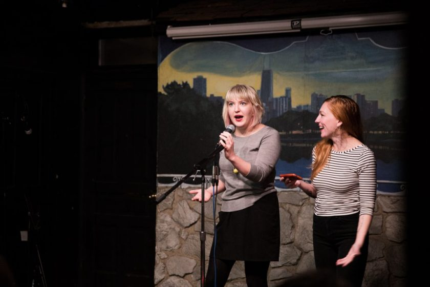 Image: Photo of Rosamund Lannin (left) and guest co-host Alicia Swiz standing on-stage at Miss Spoken at the Gallery Cabaret. Both appear in medium-long-shot on the right side of the frame. Lannin looks out toward the audience (not visible) and speaks into the microphone, while Swiz smiles and looks at Lannin. Lannin wears a grey shirt, black skirt, and black leggings. Swiz wears a black and white striped shirt and black pants. Painted on the stage wall behind the readers is a scene showing Chicago's skyline, as if viewed from behind a stone wall. Photo by Sarah Joyce. Courtesy of Miss Spoken.