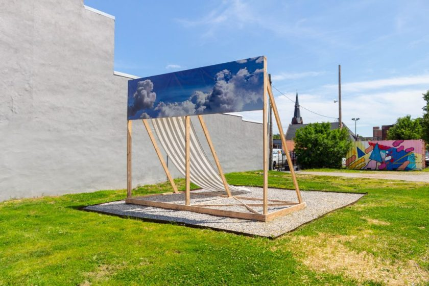 Image: Kahlil Robert Irving, MOBILE STRUCTURE; RELIEF & Memorial: (Monument Prototype for a Mass); 2019. Sculptural Installation. The structure is made up of wooden supports and with a banner of clouds going across the top, and a black and white striped banner going down the backside. Photo by Shabez Jamal.