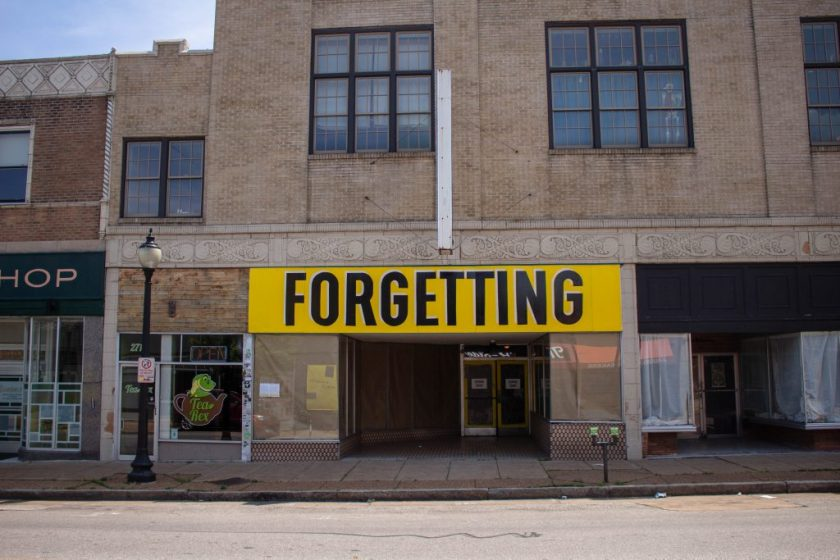 """Image: Joseph del Pesco and Jon Rubin, Monuments, Ruins and Forgetting; 2019. Installation with changing signpainting. A vacant storefront with a large yellow sign that reads """"Forgetting."""" Photo by Shabez Jamal. Photo by Shabez Jamal."""