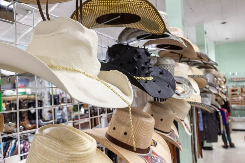 Image: Yowshien Kuo at Carrillo Western Wear, 2019. Installation with hand-painted apparel. A rack in a clothing store displays rows of cowboy hats. The hat in the middle is black with spikes. Photo by Shabez Jamal.