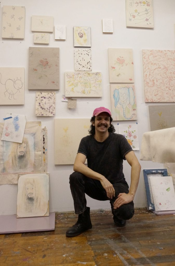 Image: Alejandro Jiménez-Flores crouching down smiling in front of their artwork hanging on a wall. They are wearing dark clothing and a pink hat. Photo by Cecilia Kearney.