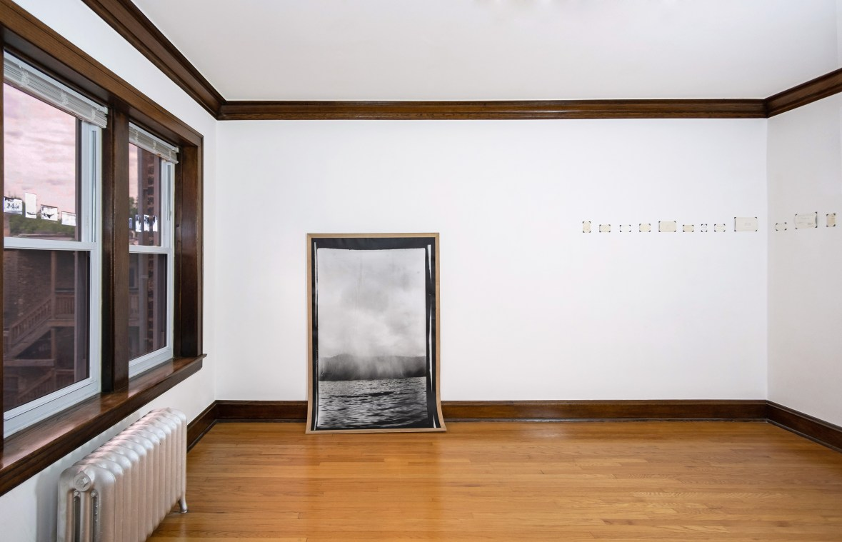 Image: Andre Keichian, 'Salt in the I' (installation view), 2019. A large black and white portrait photograph of a landscape mounted on wood curves against the base of the wall meeting the floor. To the left, a series of negatives of Keichian's family photographs adhered to the glass window. To the right, a series of the back, written sides of photographs placed across the corner of the room. Photo by Kim Becker. Image courtesy of Kyle Bellucci Johanson.