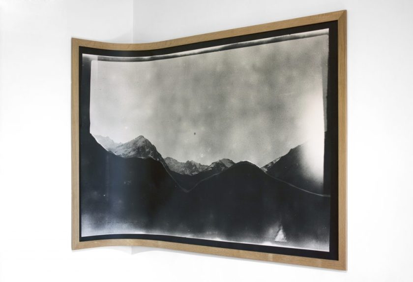 Image: Andre Keichian, 'Salt in the I' (detail), 2019. A large black and white landscape photograph mounted on wood curves against the corner of the room, as part of the exhibition installation at table. Photo by Kim Becker. Image courtesy of Kyle Bellucci Johanson.