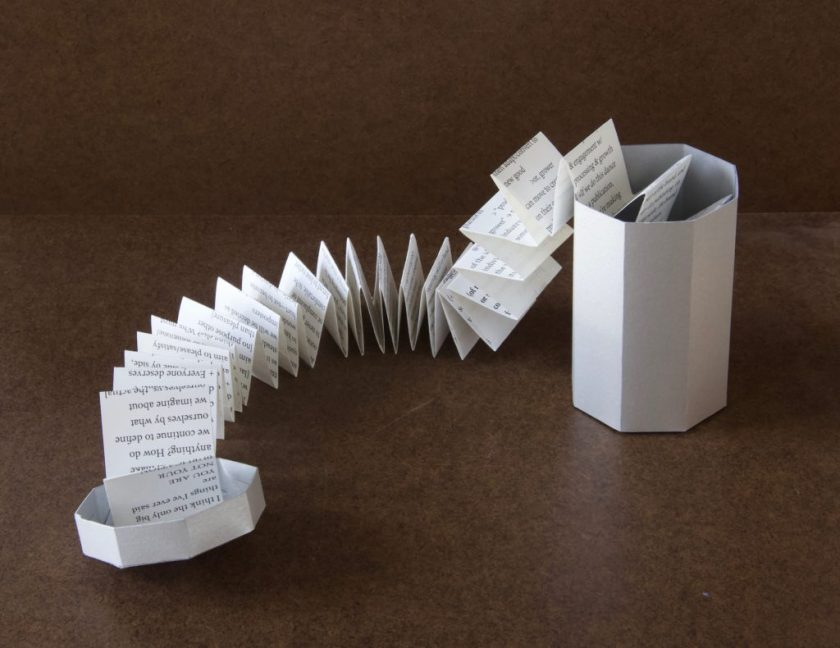 """Image: A photo of """"Trash Baby Manifesto,"""" a book by Chelsea Fiddyment, 2018. The book's casing looks like a trashcan — octagonal at the base and top, with a lid. It is made out of thin white cardboard. The lid and can sit on opposite sides of the frame. In this image, the book's contents — a length of accordion-folded paper, long and narrow, attached at one end to the lid and continuing into the """"trashcan"""" at the other end — stretches across the dark surface between them. The paper is white with black serif text in a small font. Photo by Meekling Press. Courtesy of the artist."""
