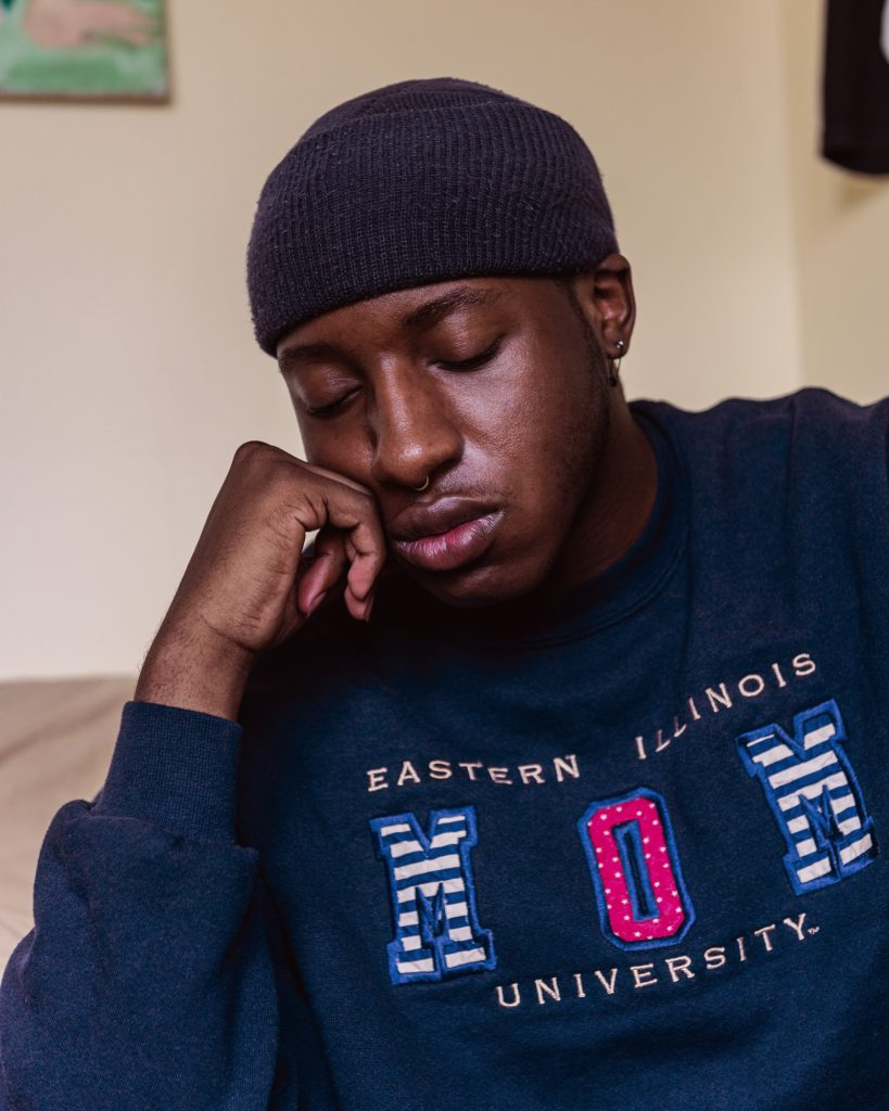 """Image:Miss Twink USA closes his eyes and rests his chin on his fist. He's wearing a beanie and a navy blue sweatshirt that reads, """"Eastern Illinois University Mom."""" Photo by Ryan Edmund."""