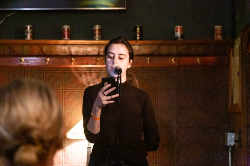 Image: Molly Gunther performing at Unreal at Schubas. Gunther stands at the front of the room, speaking into a microphone while looking past it at a phone. Behind Gunther is a copper-colored wall, made of a grid of low-relief tiles; above that are several decorative beer cans on a ledge and a dark green section of wall. Gunther wears a black with a sleeve rolled up. The back of an audience member's head is unfocused in the foreground. Photo by Joshua Clay Johnson.