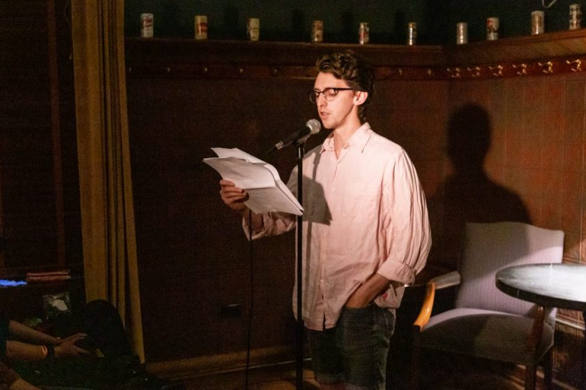 Image: Nick Russell performing at Unreal at Schubas. In this oblique, medium-length shot, Russell stands at the front of the room, speaking into a microphone while reading off a creased paper. Behind Russell is a copper-colored wall, made of a grid of low-relief tiles; above that are several decorative beer cans on a ledge and a dark green section of wall. Russell wears a pale pink collared shirt with sleeves rolled up, as well as dark-rimmed glasses. Photo by Joshua Clay Johnson.