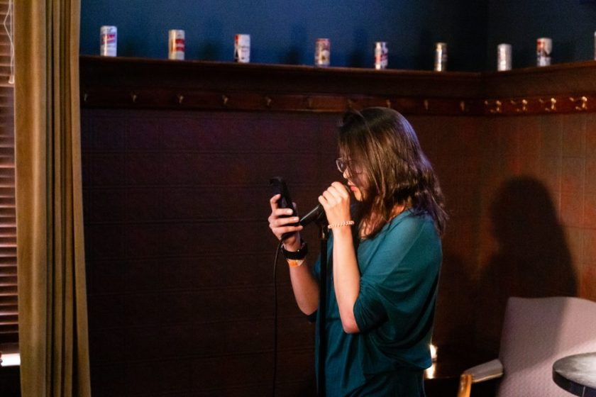 Image: Antonina Neva performing at Unreal at Schubas. In this oblique, medium-length shot, Neva stands at the front of the room, speaking into a microphone while reading off a phone. Behind Neva is a copper-colored wall, made of a grid of low-relief tiles; above that are several decorative beer cans on a ledge and a dark green section of wall. Neva wears a teal three-quarter sleeve shirt and dark-rimmed glasses. Photo by Joshua Clay Johnson.