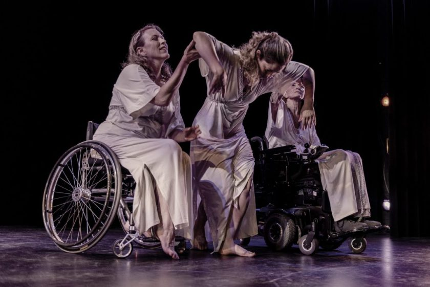 Image: Three dancers dressed in long white dresses are in motion on a dark stage; the dancer on the left (Ladonna Freidhem) is seated in an active wheelchair; the dancer on the right (Ginger Lane) is seated in a motorized wheelchair; the dancer at center (Anita Fillmore Kenney) has her head down, while her partners support her. Photo by Ryan Edmund.