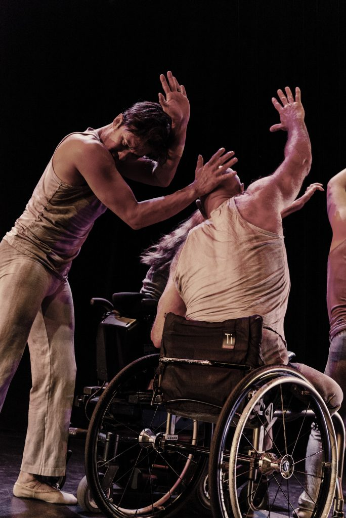 Image: Dancers dressed in light grey clothing are in motion on a dark stage; at left a dancer bows his head and lifts his hands, one hand is pressed against the back of another dancer's head; that dancer, seated in an active wheelchair, also raises his arm in a similar motion; other dancers can be seen in the background. Photo by Ryan Edmund.