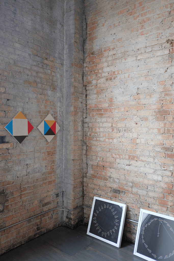 "Image: The corners of a fading brick room meeting. On the left, about five feet off the ground are two canvases with an inch between them. These are Paolo Arao's ""Greater Than (Diptych)"" Leaning against the brick wall to the right on the floor are two of Jeffery Augustine Songco's ""Choreography Playbook"" series. Image courtesy of FLXST Contemporary."