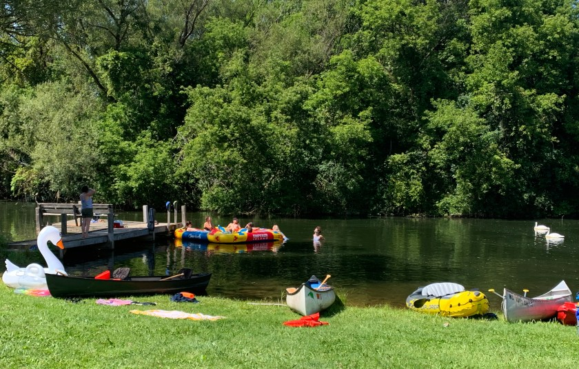 Image: Canoes, kayaks, and inflatable rafts are sitting on grass pictured in the foreground. Campers are floating on a large raft next to a wooden pier on a lake against a background of trees. Photo by Rachel Hausmann Schall.