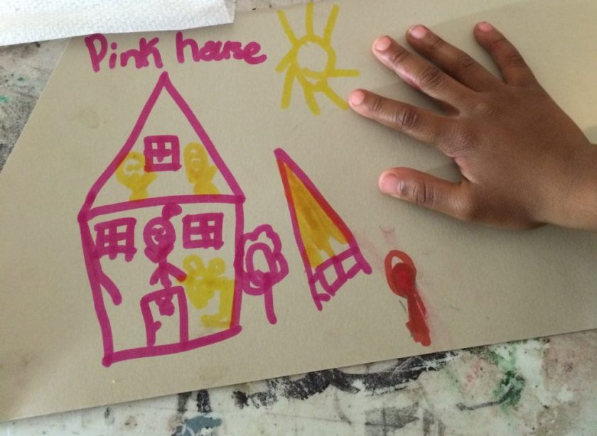 "Image: A drawing at Pink House, St. Louis, held down by a child's hand. The drawing is bright pink and yellow on white paper. The drawing shows a cross-section of the house with people inside on the first and second floors; outside the pink house are the words ""Pink house,"" a sun, trees, and more. Photo by Patrick Fuller. Courtesy of the artist."