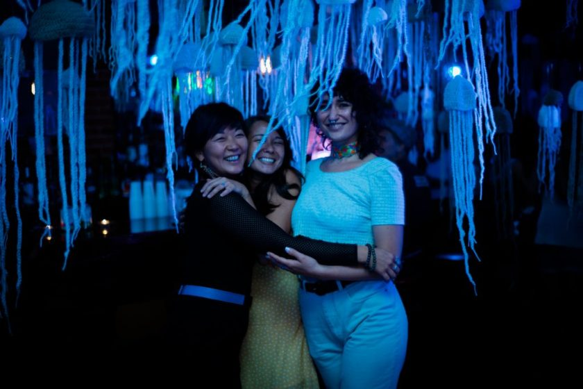 "Image: Regina Martinez at ""the clothesline"" in St. Louis in 2019. Martinez (right) poses with co-founders April Fulstone and Angelina Fasano. They stand together, smiling at the camera with arms around each other, in a dark space lit by bluish light. Hanging from the ceiling and all around them are dozens of crocheted jellyfish made of light-colored yarn. Fulstone wears all black with a blue belt, Fasano wears a yellow and white patterned outfit, and Martinez wears a light top and light pants with a bright, multi-colored choker. Photo by Carly Faye. Courtesy of the artist."