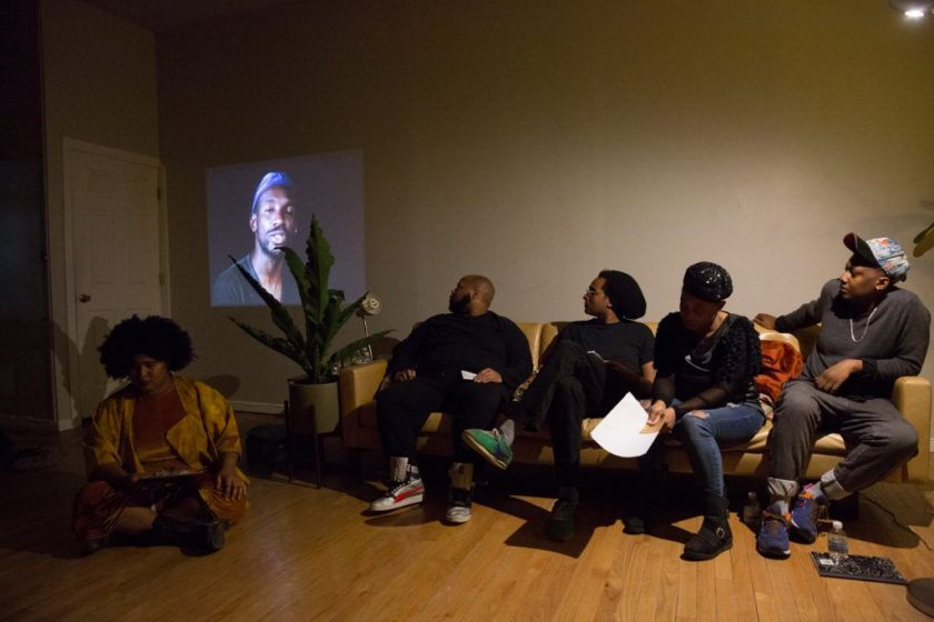 """Image: In-Session, """"Eclipsing: Migration, Movements and Desire,"""" at Threewalls in March 2018, presented by Amina Ross with J'Sun Howard, Khadijah Ksyia, Jared Brown, and A.J. McClenon, in response to the guiding work """"Tongues Untied"""" by Marlon Riggs. In this shot, the artists sit in a row, with an image from """"Tongues Untied"""" projected on the wall behind them in a low-lit room. Ross (left) sits on the wood floor and Howard, Brown, Ksyia, and McClenon (left to right) sit on a tan couch. Howard, Brown, and McClenon look toward the projected video and Ross and Ksyia look down. Ross wears a mustard-colored one-piece and jacket, Howard and Brown both wear all black, Ksyia wears a black top with blue jeans, and McClenon wears a grey top with grey jeans. Brown, Ksyia, and McClenon all wear headwear, and Ksyia holds paper in hand. Photo by Milo Bosh. Courtesy of Threewalls."""