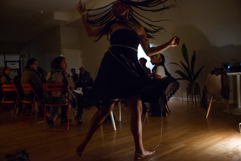 "Image: In-Session, at Threewalls in November 2018, by Najee Searcy and collaborators, in response to the guiding work ""Hush: Don't Say Anything to God: Passionate Poems of Rumi"" by Shahram Shiva. Ester Alegria of Zo//Ra performs in the foreground. Alegria is in mid-motion, as if spinning or twisting quickly, with arms out and one foot off the ground, and long braids and the bottom of a black dress flying outwards. The artist wears a black strapless dress, with a length of silver beads tied around its bodice and extending onto the ground, under and around the performer's left foot. In the background of the dim room, audience members sit in a circle, most of them turned toward the performer. Photo by Milo Bosh. Courtesy of Threewalls."