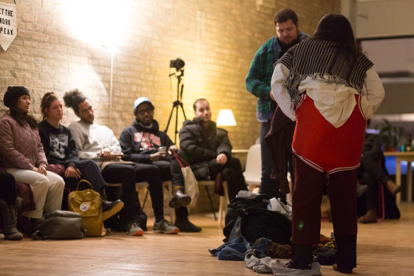 "Image: In-Session, at Threewalls in February 2018, by Jose Luis Benavides and collaborators, in response to the guiding work ""Mexican American Disambiguation"" by José Olivarez. In the foreground, two performers stand, one facing the camera and one facing away from it, each wearing layers of varied clothes, including pants of varying lengths, multiple button-up shirts, and what appears to be a wrestling uniform. On the floor between them is a pile of still more clothes. In the background, several audience members watch from their chairs. Some audience members wear coats and other cold-weather clothes. Photo by Milo Bosh. Courtesy of Threewalls."