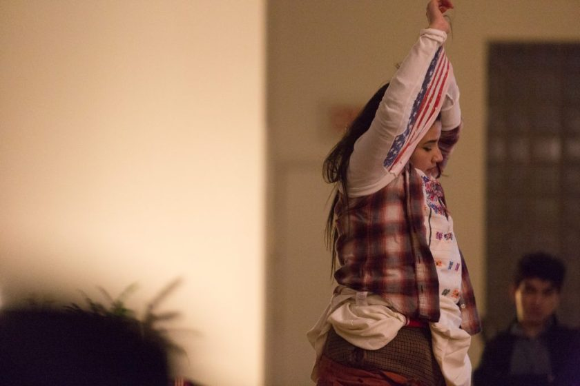 "Image: In-Session, at Threewalls in February 2018, by Jose Luis Benavides and collaborators, in response to the guiding work ""Mexican American Disambiguation"" by José Olivarez. In this medium shot, a participant is in the act of dressing or undressing, pulling a white shirt with a U.S. American flag pattern over their head. The participant's arms are in the air, entangled in the shirt, and underneath it the participant wears several tops and bottoms. One audience member is fuzzy in the background with, possibly, one in the foreground. Photo by Milo Bosh. Courtesy of Threewalls."