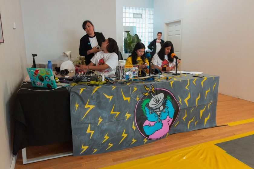 """Image: In-Session, at Threewalls in June 2018, by El Cardenal De Aztlán and collaborators, in response to the guiding work """"Borderlands/La Frontera"""" by Gloria Anzaldúa. Three artists sit behind a long table in the foreground and two stand behind them, one near, one farther back. On the table is a detailed dark grey covering (illustrated with yellow z-shapes like lightning bolts, as well as a circular inset showing a blue character unzipping its head open to reveal an active broadcast dish) and on that sit two microphones, two laptops, a soundboard, and other pieces of technology. The two artists seated behind the microphones each wear a t-shirt that matches the off-camera performers (a yellow t-shirt with a jaguar or a white t-shirt with a cardinal) and look down. The third artist wears the cardinal t-shirt and sits behind a soundboard, twisting back to talk to a person behind them. A yellow section of floor is visible in the lower-right corner of the frame. Photo by Milo Bosh. Courtesy of Threewalls."""