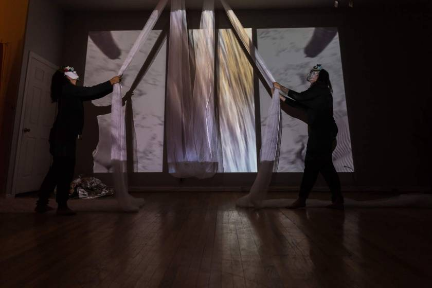 "Image: In-Session, at Threewalls in March 2019, by Maya Mackrandilal with collaborators Udita Upadhyaya and Enid Muñoz and original performance for video by Bhanu Kapil, in response to the guiding work ""Schizophrene"" by Bhanu Kapil. In this wide shot, Muñoz (left) and Mackrandilal (right) perform. Both stand near a far wall, wearing black clothes and white masks with multi-colored decorations, looking up at a very long, diaphanous white cloth that is attached to the ceiling above them in two places with its middle portion hanging low between them. Each performer holds one part of the white cloth, with each end of its remainder snaking off-camera to the left and right behind each performer. A wall-sized video, showing a textured white scene, is projected over the performers and the cloth. Balled up in one corner of the floor is a silver reflective cloth. Photo by Milo Bosh. Courtesy of Threewalls."