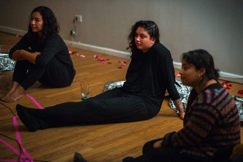 """Image: In-Session, at Threewalls in March 2019, by Maya Mackrandilal with collaborators Udita Upadhyaya and Enid Muñoz and original performance for video by Bhanu Kapil, in response to the guiding work """"Schizophrene"""" by Bhanu Kapil. Muñoz (left), Mackrandilal (center), and Upadhyaya (right) sit on the wood floor during the discussion portion of the event. They sit in oblique profile to the camera, looking off-camera toward the audience in the low-lit room. Muñoz and Mackrandilal both wear all black, and Upadhyaya wears a patterned sweater with dark bottoms. A length of fluorescent pink ribbon sits in the lower-left corner of the frame. Photo by Milo Bosh. Courtesy of Threewalls."""
