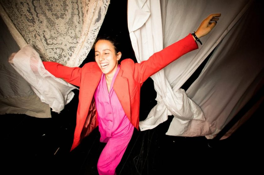Image: Ida Cuttler, with a toothy smile and wearing a crimson blazer and pink pajamas, has her arms extended out.  Behind her is an opening between several twisting bedsheets hung to the right and a taffeta sheet hung to the left. Her left hand has caught some of a transparent sheet. Photo courtesy of Brave Lux, Inc.