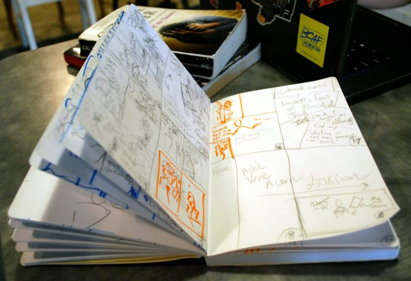 Image: A notebook sits on a table, open to pages filled with sketches and notes. Most sketches and notes are done in pencil, but there are a few that are done in orange marker. Photo by Jessica Hammie.