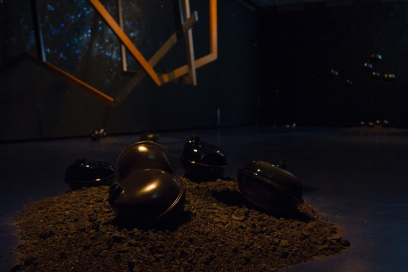 "Image: 'Fallen objects' from outer space within the installation ""Dark Matter: Celestial Objects as Messengers of Love in These Troubled Times"" by Folayemi Wilson at the Hyde Park Art Center. Dirt lay on the floor with sculptural objects on and suspended above. Photo by Michael Sullivan."