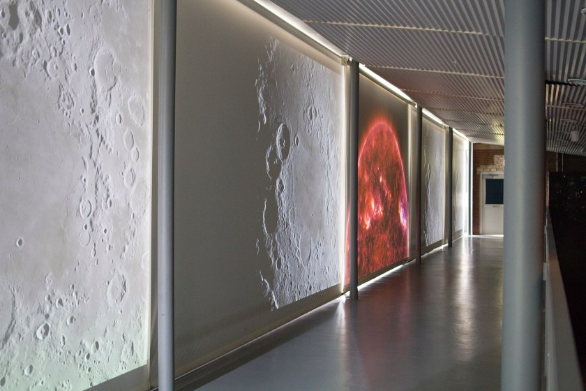 """Image: Installation view of """"Dark Matter: Celestial Objects as Messengers of Love in These Troubled Times"""" by Folayemi Wilson. Catwalk with rotating NASA videos of the sun and moon. Photo by Michael Sullivan."""