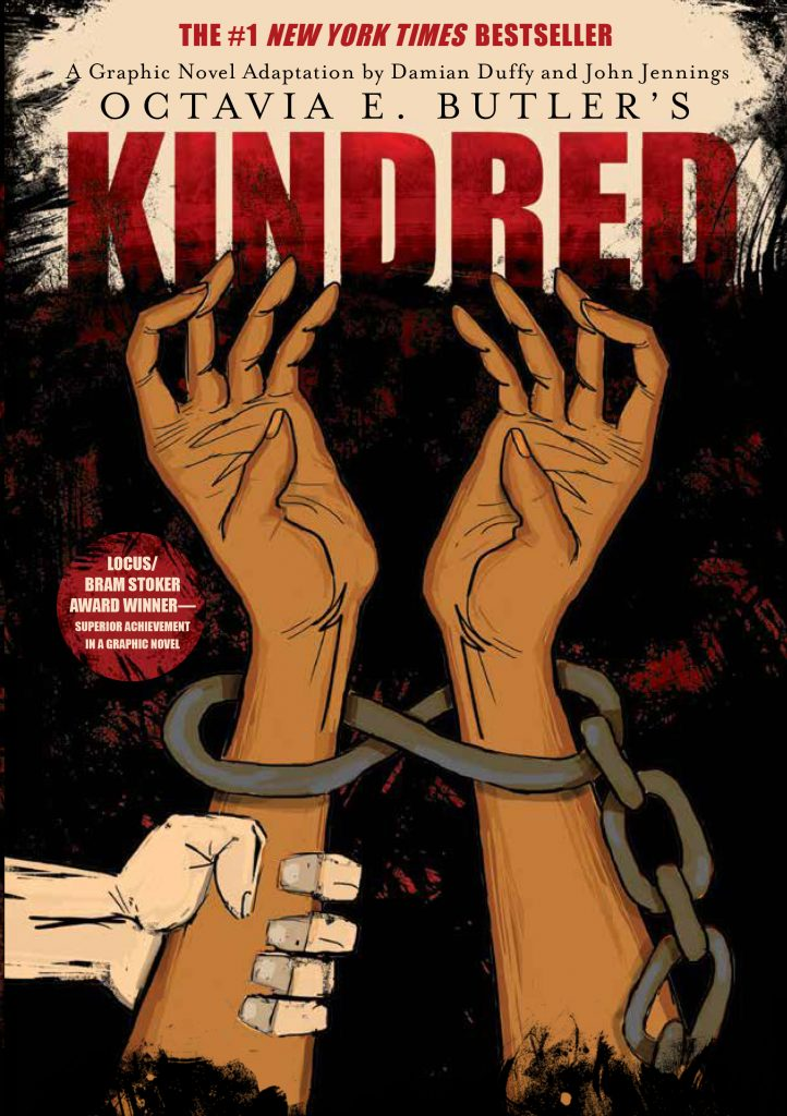 "Image: The cover of ""Kindred: A Graphic Novel Adaptation"" features two brown arms reaching upward, with chains around the wrists against a black and red backdrop. A white hand grabs the left arm. Image courtesy of Damian Duffy."