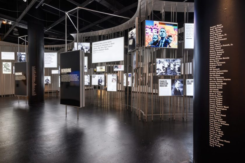 Image: Installation view of Men of Change. The installation made of metal poles is in the middle of the room. Light boxes of various sizes featuring photos and text are hung on the metal poles. Two large displays are in front of the poles: one says IMAGINING and the other says FATHERING. Two large, black architectural columns, one on the right of the image and one on the left of the image feature the names of men of color in alphabetical order. Photo by Phil Armstrong. Photo courtesy of the Smithsonian Institution Traveling Exhibition Service.