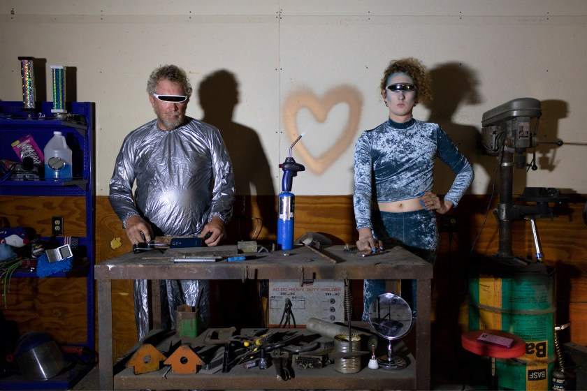 Image: FarmBot 3000 and FemmeBot 6000, 2018 by Nadia Stiegman. Two Cyborgs are shown in a tool shed standing side by side with various tools and toys around them. A heart is spray painted to the back wall. Image courtesy of the artist.