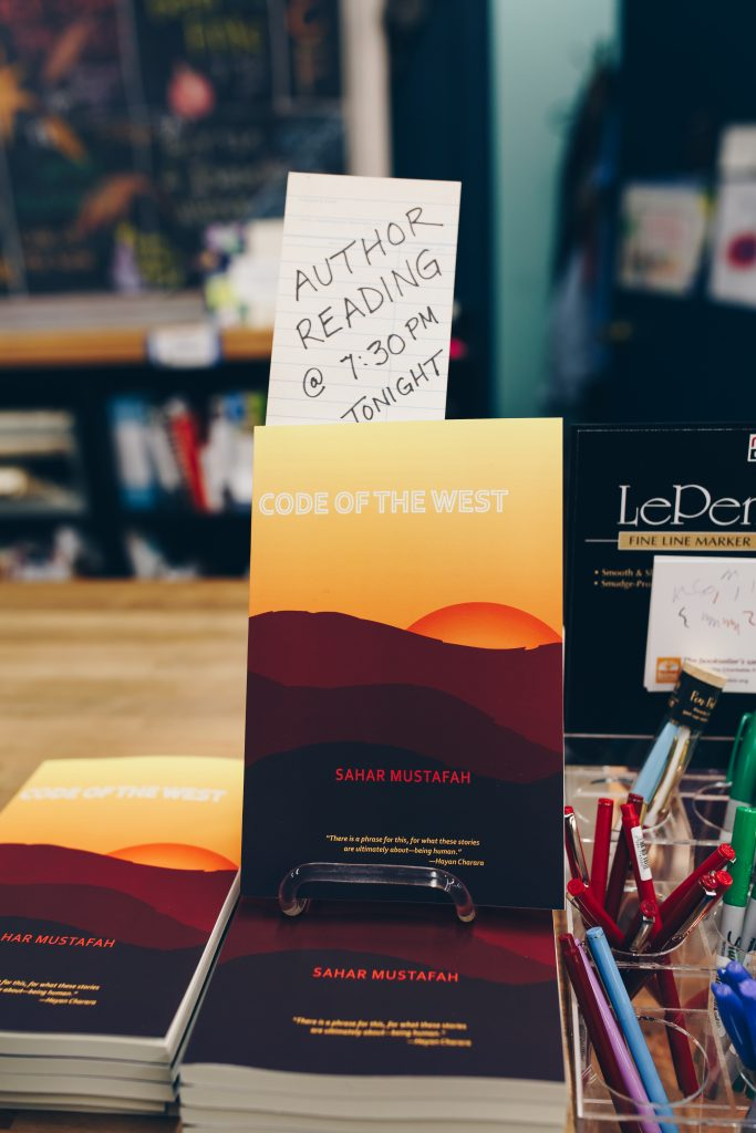 "Image: Mustafah's short story collection, ""Code of the West"" (Willow Books, 2017). One copy of the book is displayed upright atop several other copies, which lay flat on a bookstore countertop. A hand-written paper reads, ""Author reading @ 7:30pm tonight,"" in all capital letters. The book cover's illustration shows a sliver of orange sun behind reddish and dark brown hills, with a yellow sky above. Photo by Michelle Strahan."