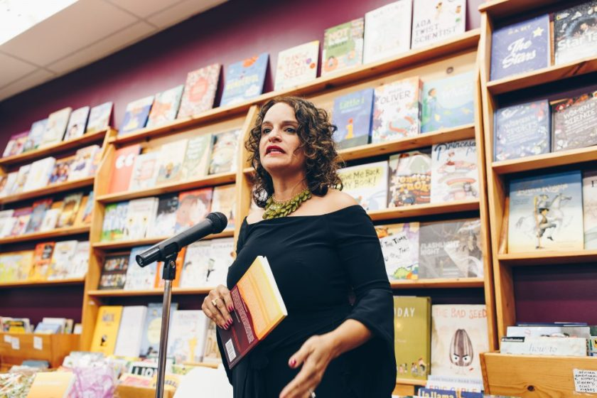 "Image: Mustafah reading at the book launch event for her short story collection, ""Code of the West,"" at Women & Children First Bookstore in 2017. Mustafah stands, speaking into a microphone, a wall of picture books behind her. In her hand, she holds a copy of ""Code of the West."" Mustafah wears a dramatic green necklace and an off-the-shoulder black shirt with three-quarter-length sleeves that drape open at the hem. Photo by Michelle Strahan."